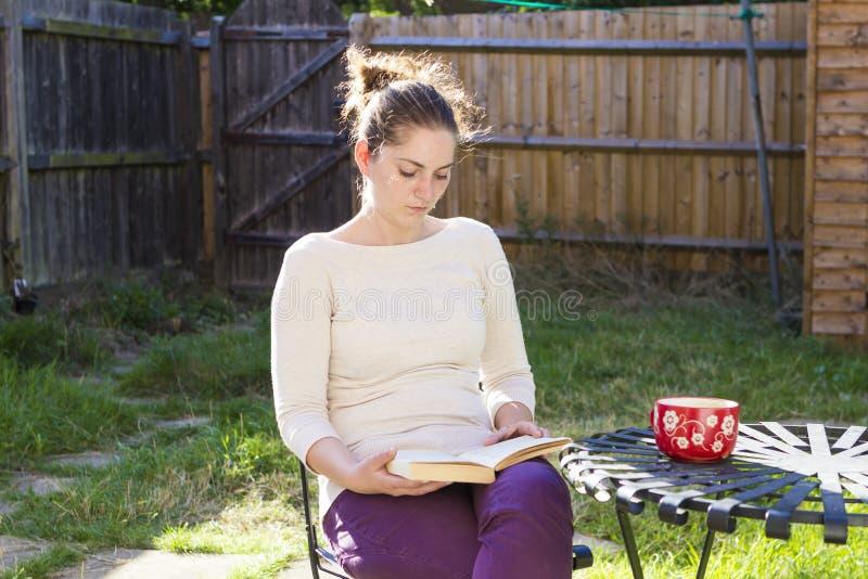 Menina bonito que lê um livro exterior imagens de stock royalty free