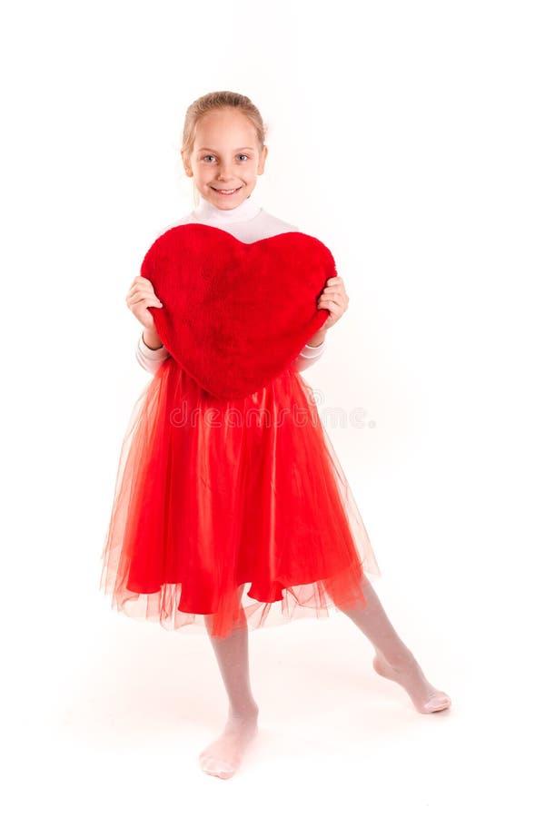 Menina bonito que mantém o coração vermelho isolado foto de stock royalty free