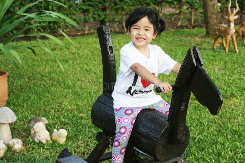 Menina bonito que monta um cavalo de madeira fotos de stock royalty free