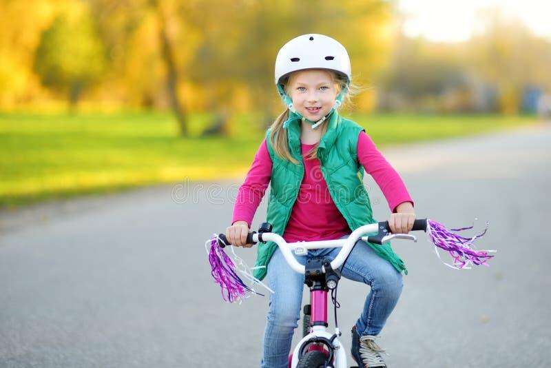 Menina bonito que monta uma bicicleta em um parque da cidade no dia ensolarado do outono Lazer ativo da família com crianças fotos de stock royalty free