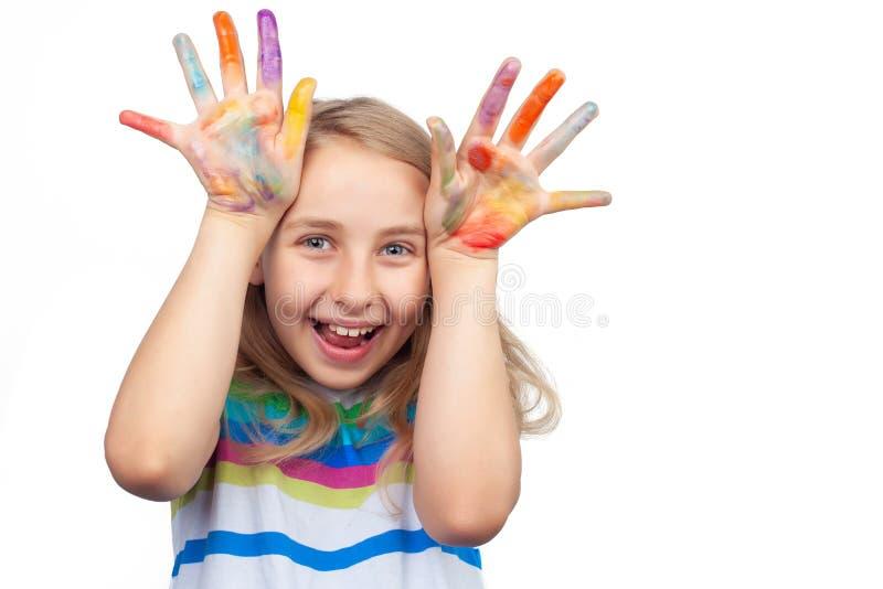 Menina bonito que mostra as mãos pintadas nas cores brilhantes isoladas no branco foto de stock royalty free