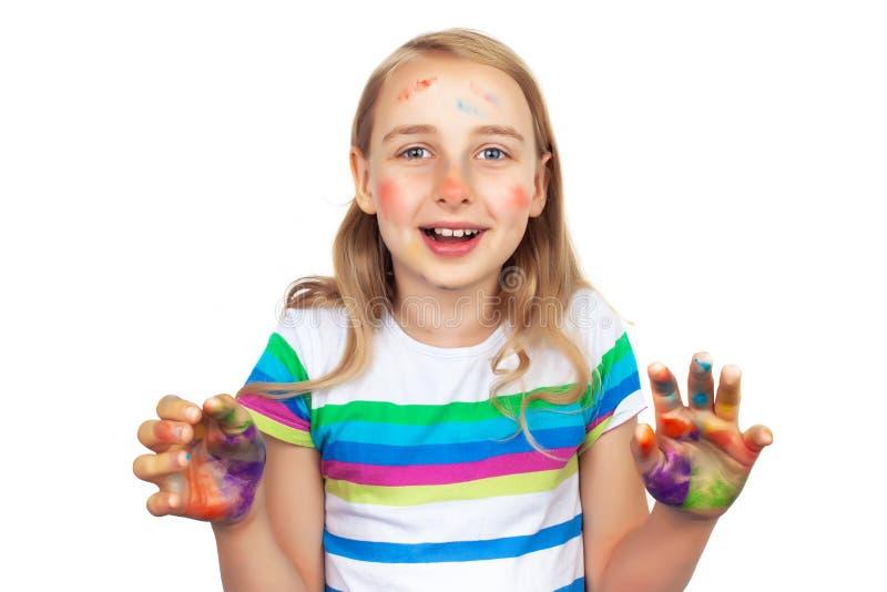 Menina bonito que mostra as mãos pintadas nas cores brilhantes isoladas no branco fotos de stock