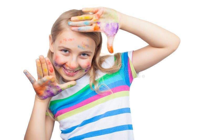 Menina bonito que mostra as mãos pintadas nas cores brilhantes isoladas no branco imagens de stock royalty free