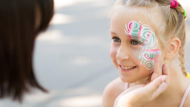 Menina bonito que obtém sua cara pintada no parque imagens de stock royalty free