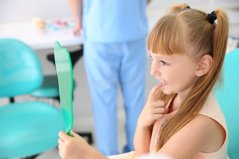 Menina bonito que olha no espelho no escritório do dentista fotos de stock
