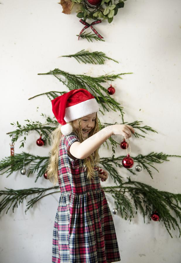 Menina bonito que pendura acima dos ornamento do Natal fotos de stock