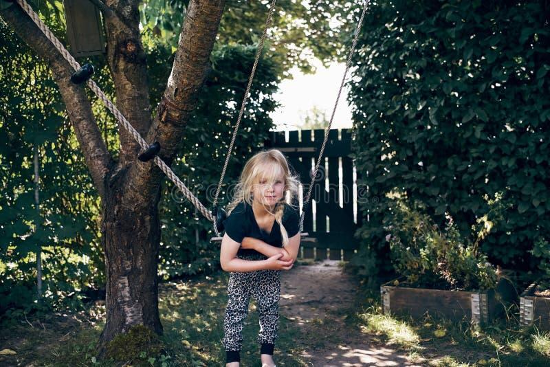 Menina bonito que pendura em uma parte externa do balanço da árvore foto de stock