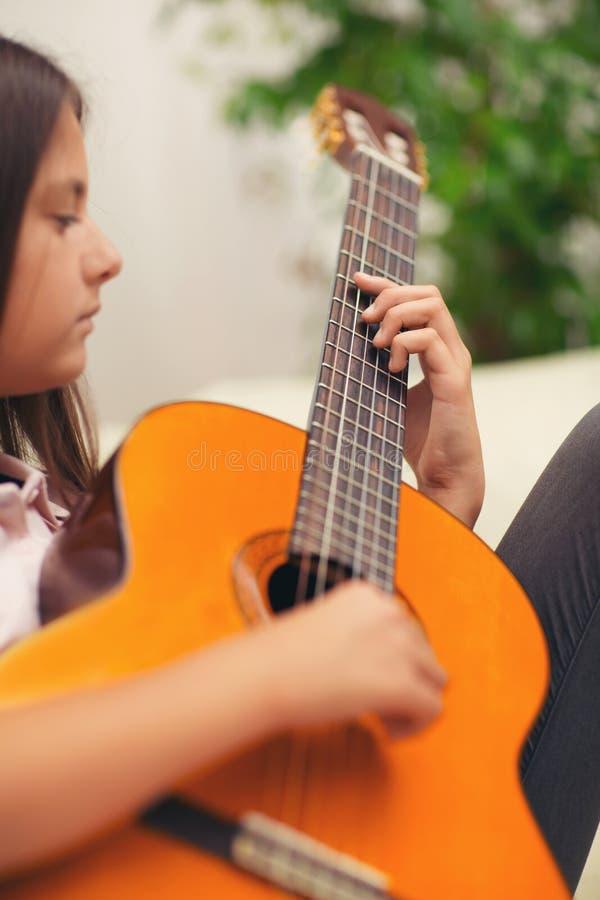 Menina bonito que pratica suas lições da guitarra foto de stock royalty free