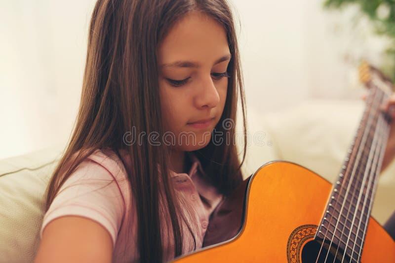 Menina bonito que pratica suas lições da guitarra fotos de stock royalty free