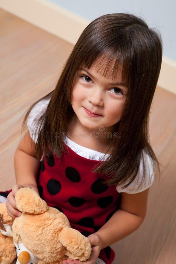 Menina bonito que prende o brinquedo macio imagem de stock royalty free