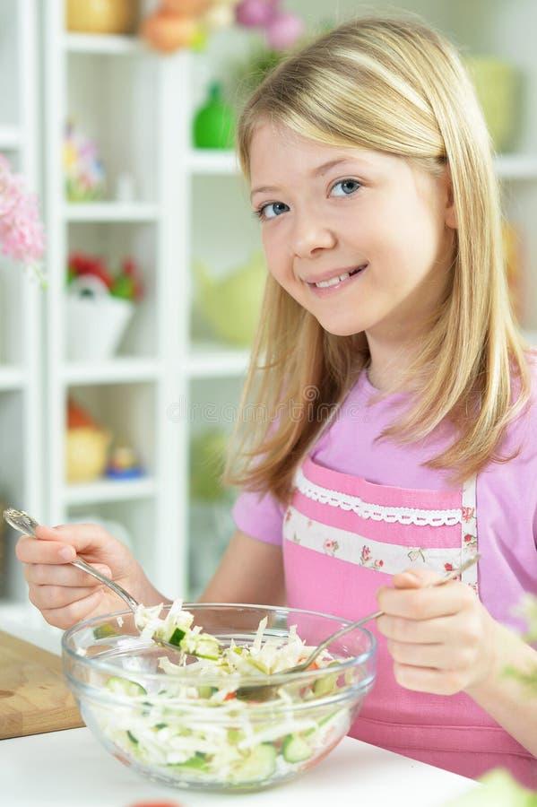 Menina bonito que prepara a salada fresca na mesa de cozinha em casa imagem de stock royalty free