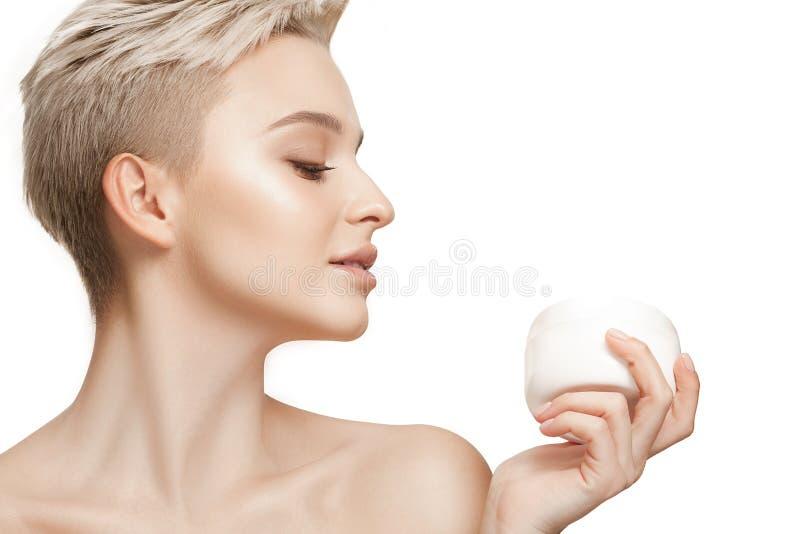 Menina bonito que prepara-se para começar seu dia Está aplicando o creme do creme hidratante na cara fotos de stock royalty free