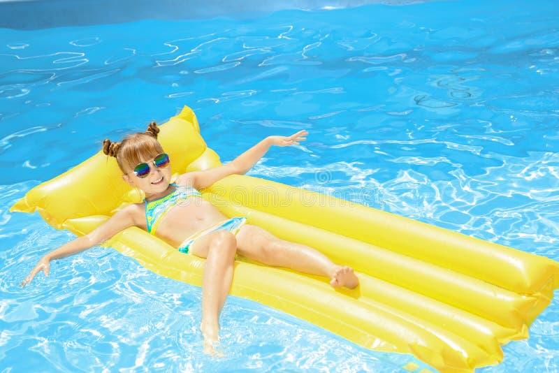 Menina bonito que relaxa no colchão inflável na piscina fotos de stock royalty free