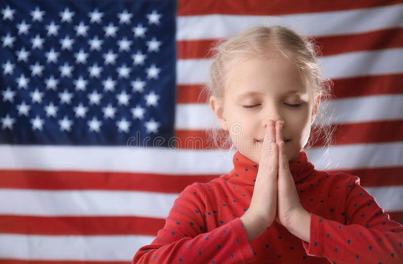 Menina bonito que reza na bandeira americana imagens de stock royalty free