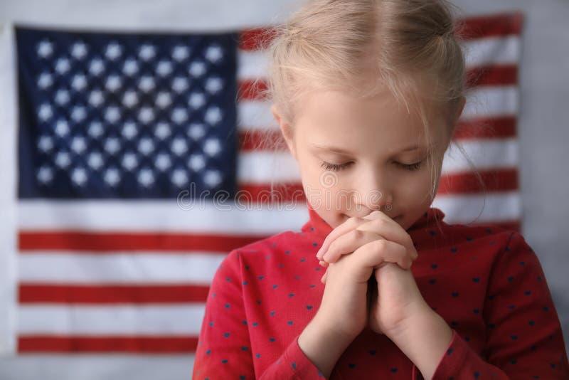 Menina bonito que reza na bandeira americana fotografia de stock