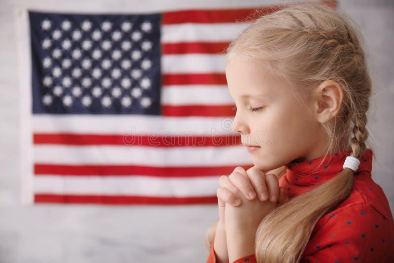 Menina bonito que reza na bandeira americana fotos de stock