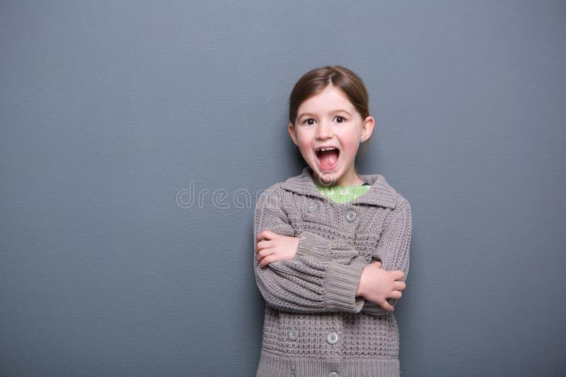 Menina bonito que ri com os braços cruzados fotografia de stock royalty free
