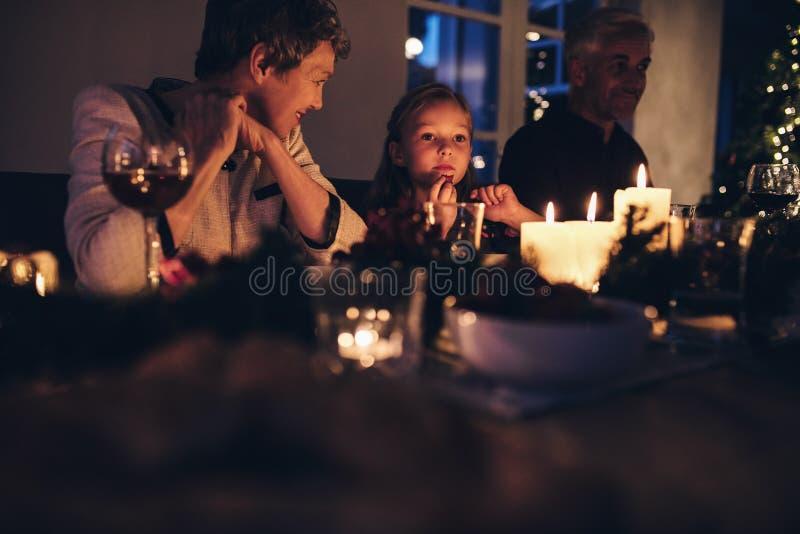 Menina bonito que senta-se com a família para o jantar de Natal fotografia de stock