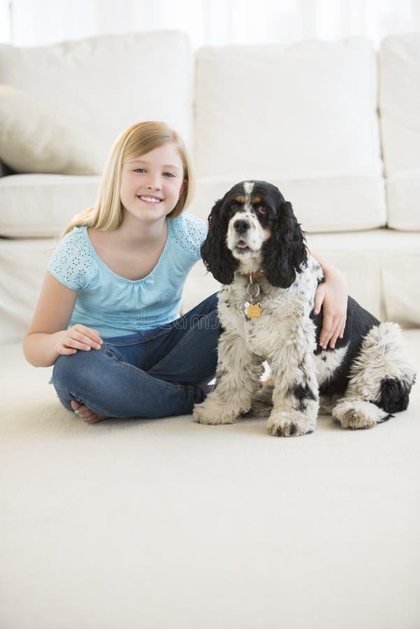 Menina bonito que senta-se com o cão de estimação na sala de visitas imagens de stock royalty free