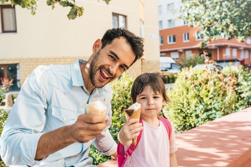 Menina bonito que senta-se com o paizinho na rua da cidade e que come o gelado exterior Tempo feliz da despesa da criança junto c foto de stock royalty free
