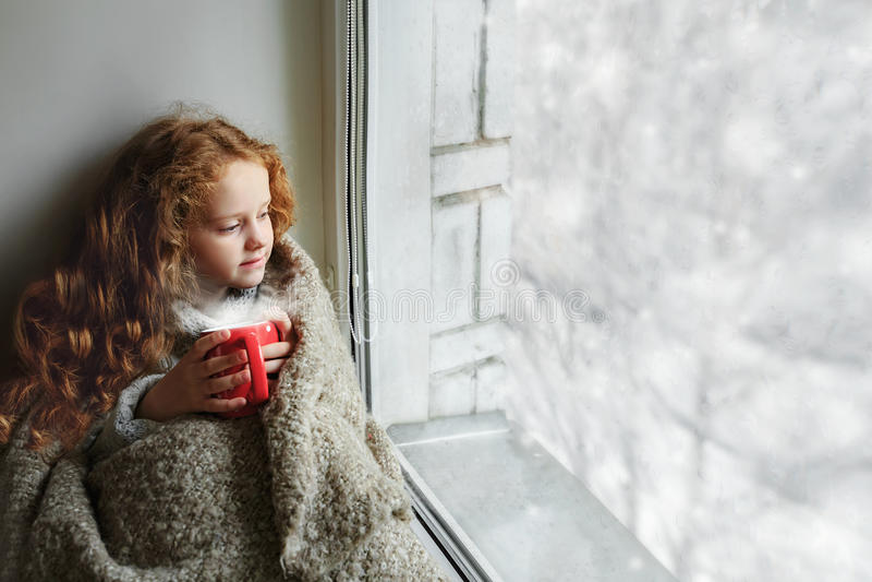 Menina bonito que senta-se com um copo do cacau quente pela janela a imagem de stock
