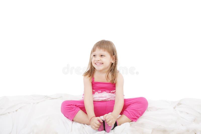Menina bonito que senta-se na cama fotografia de stock royalty free