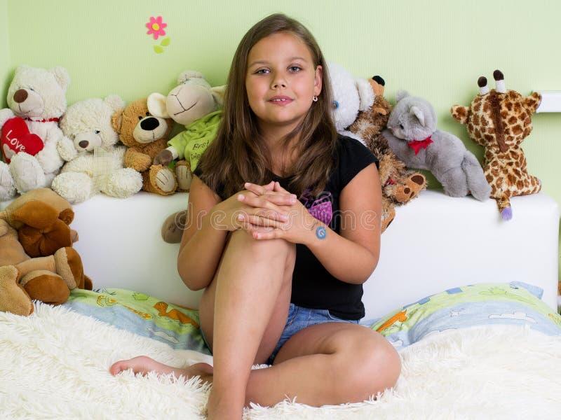 Menina bonito que senta-se na cama imagens de stock royalty free