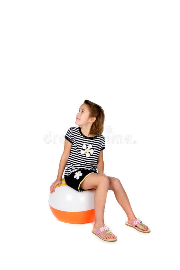 Menina bonito que senta-se na esfera de praia que espera para jogar fotografia de stock royalty free
