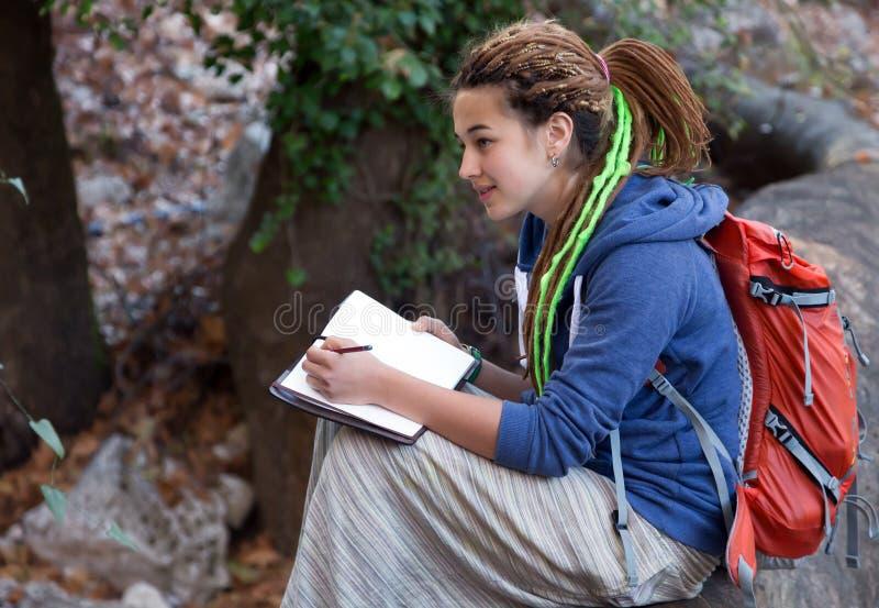 Menina bonito que senta-se na floresta e no esboço de tiragem em seu livro de nota fotografia de stock