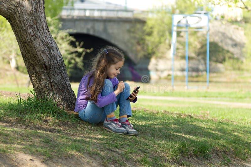 Menina bonito que senta-se na grama com um telefone celular em suas mãos e que envia a mensagem no móbil do telefone imagens de stock royalty free