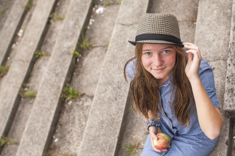 Menina bonito que senta-se nas etapas de pedra, vista superior, olhando a câmera fotografia de stock