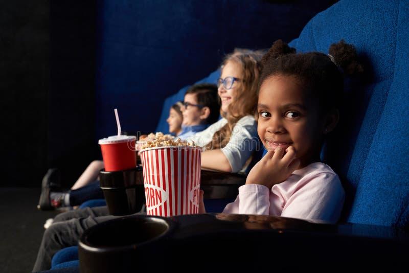 Menina bonito que senta-se no cinema com os amigos, olhando a câmera fotos de stock royalty free