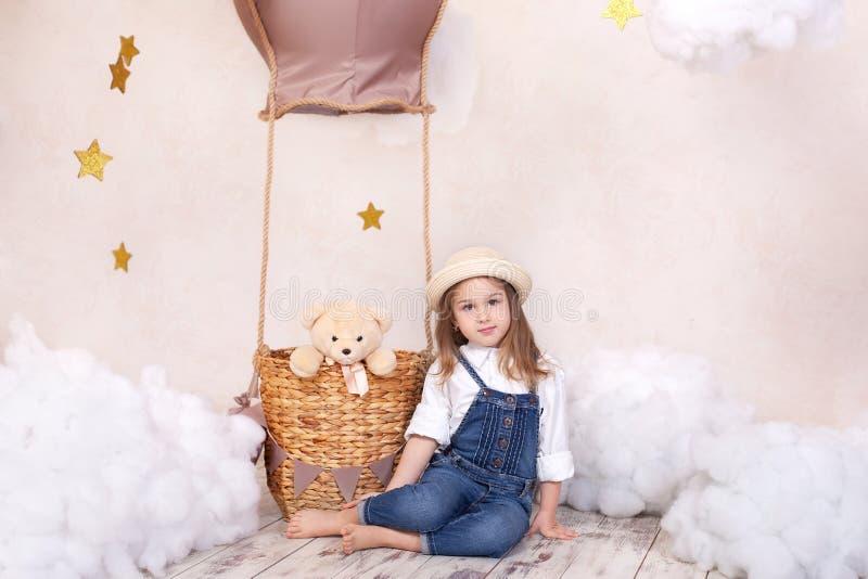 Menina bonito que senta-se no estúdio no fundo de um balão, de estrelas e de nuvens e guardando um urso de peluche A menina é dre foto de stock