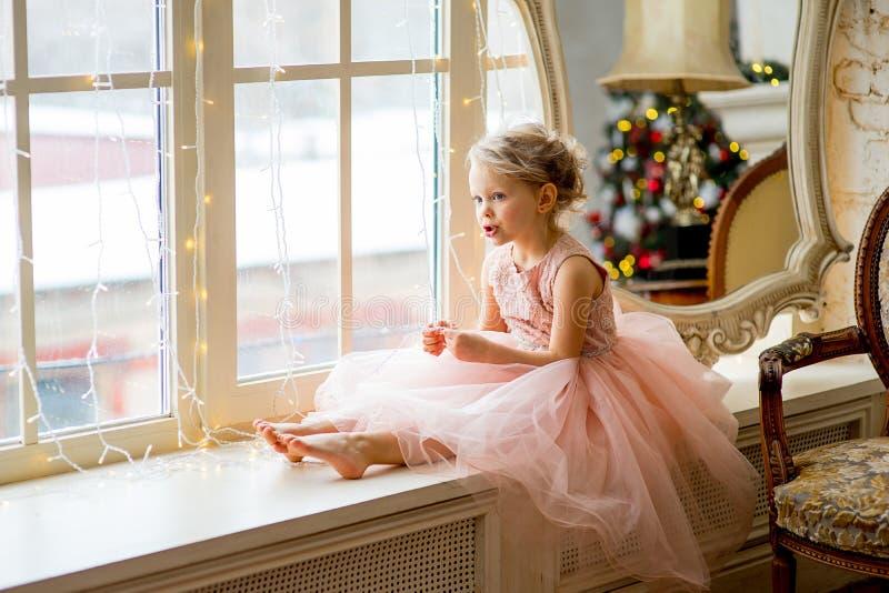 Menina bonito que senta-se pela janela imagens de stock royalty free