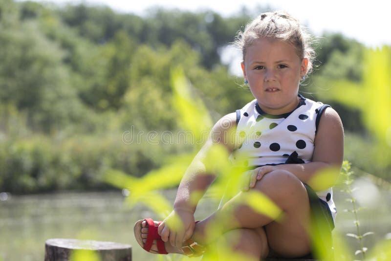Menina bonito que senta-se pelo lago e que olha a câmera fotografia de stock royalty free