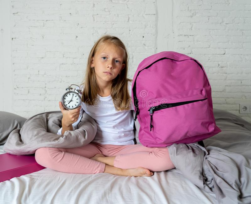 A menina bonito que sente muito cansou-se cedo na manhã que não quer preparar-se para a escola fotos de stock