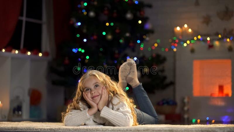 Menina bonito que sonha do milagre, Santa Claus de espera perto da árvore de Natal fotos de stock
