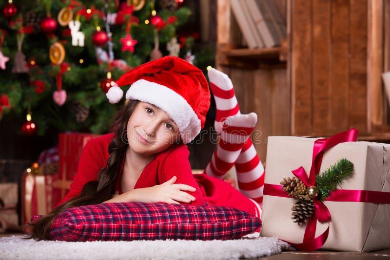 Menina bonito que sonha perto da árvore de Natal foto de stock