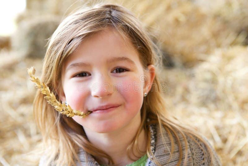 Menina bonito que sorri com palha na boca fotografia de stock