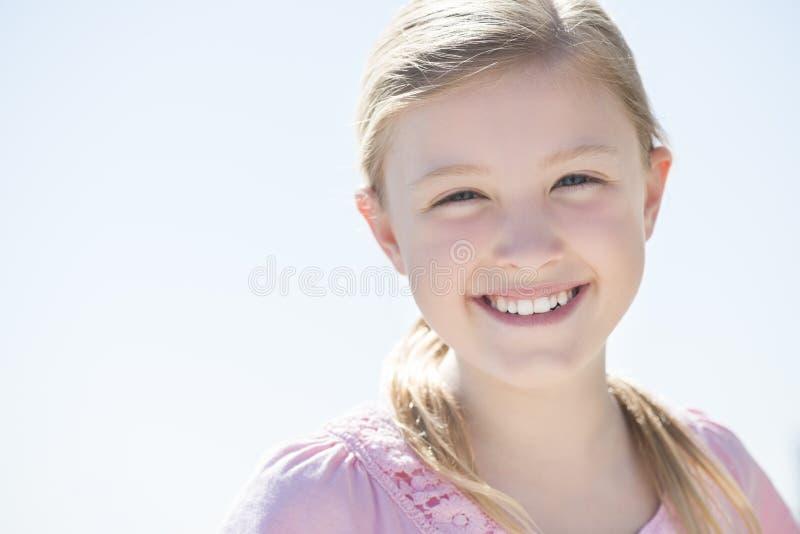 Menina bonito que sorri contra o céu claro imagem de stock