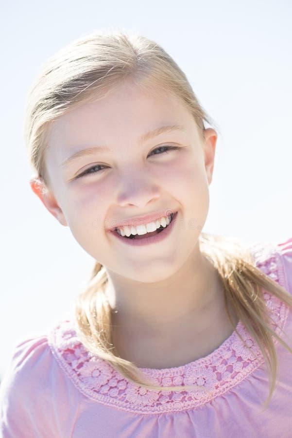 Menina bonito que sorri contra o céu claro fotos de stock