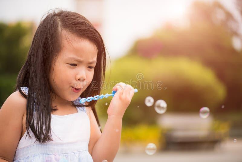 Menina bonito que tem o divertimento com bolhas de sabão de sopro imagens de stock royalty free