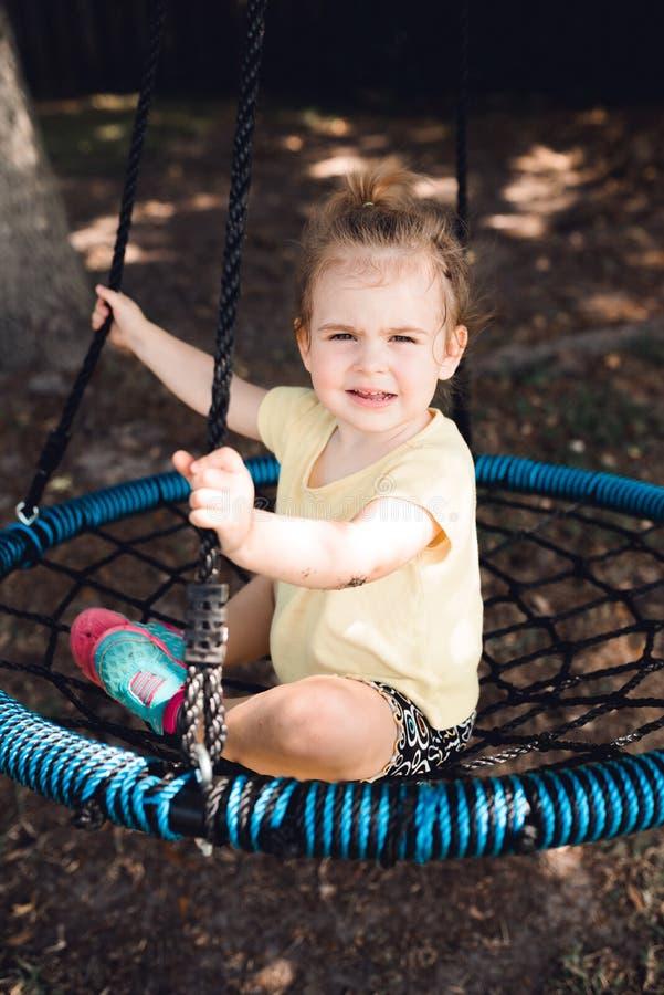 Menina bonito que tem o divertimento em um balanço redondo da árvore imagem de stock royalty free