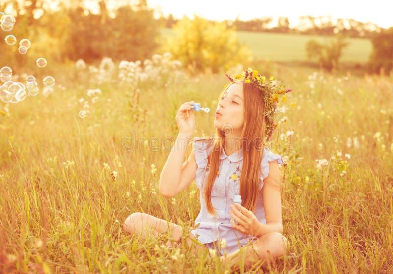 Menina bonito que tem o divertimento que joga com bolhas de sabão imagem de stock