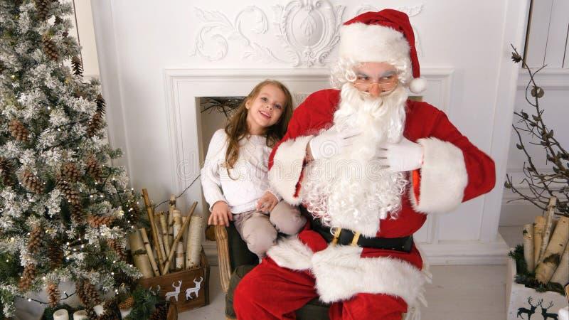 Menina bonito que tem o divertimento junto com Santa Claus imagem de stock