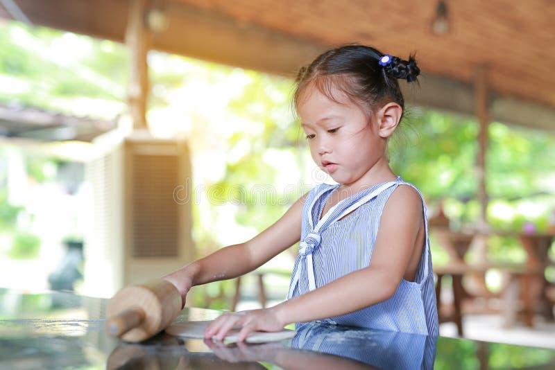 Menina bonito que usa o pino do rolo de madeira na massa para a pizza Processo caseiro de pizza da preparação foto de stock