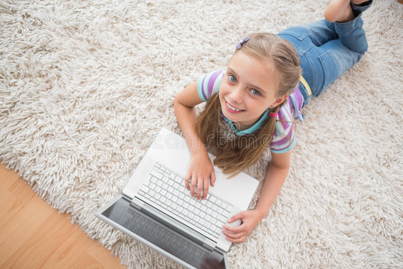 Menina bonito que usa o portátil ao encontrar-se no tapete fotografia de stock