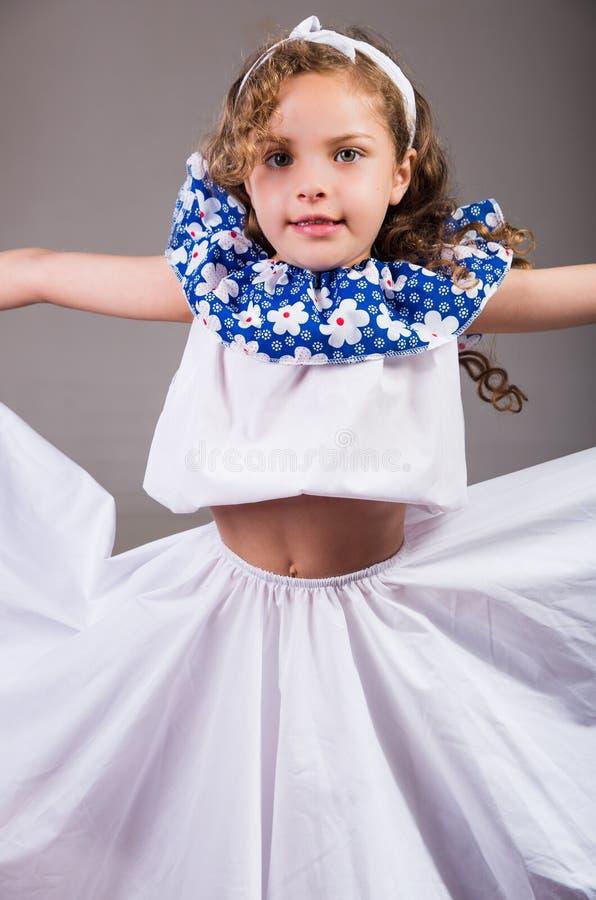 Menina bonito que veste o vestido branco e azul bonito com a faixa principal de harmonização, levantando ativamente para a câmera imagens de stock