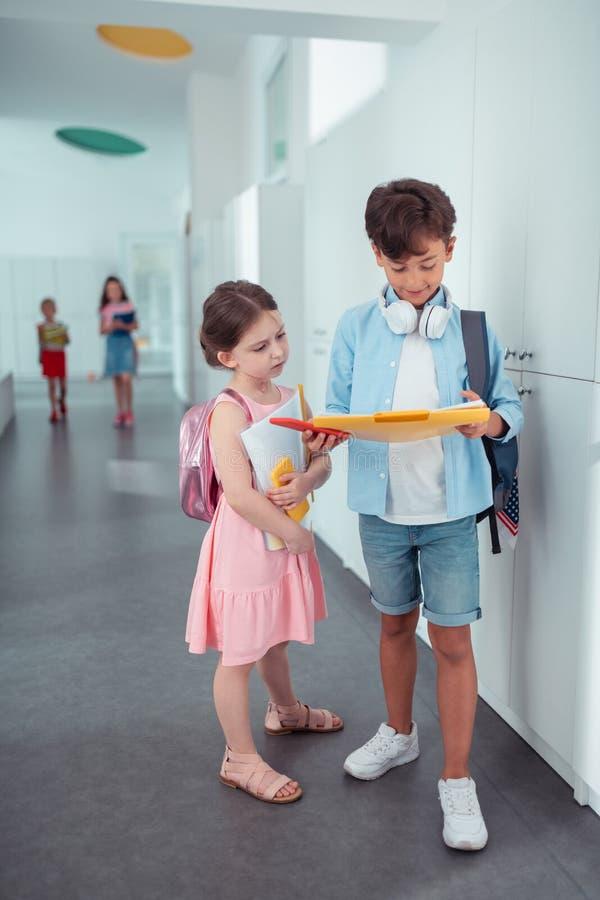 Menina bonito que veste a posição cor-de-rosa do vestido perto da estudante considerável foto de stock