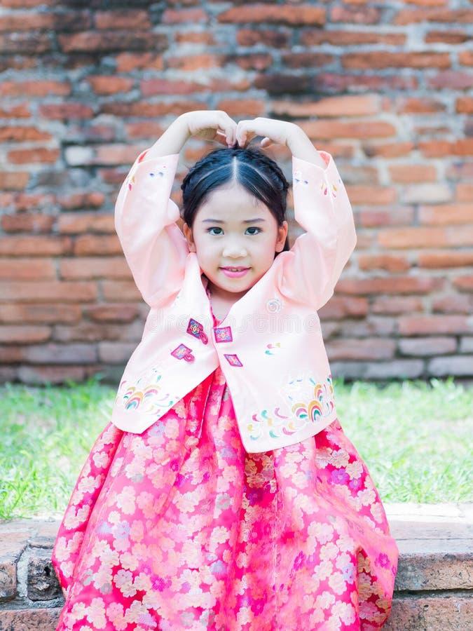 A menina bonito que veste trajes de Coreia mostra a mão do símbolo do amor imagem de stock